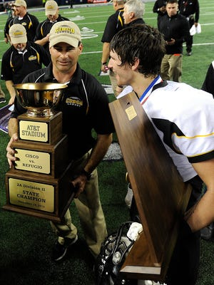 Cisco head coach Brent West and Kyle Green (22) hold the state championship trophies after the Loboes' 56-36 win over Refugio in the Class 2A Div. II state championship game on Thursday, Dec. 19, 2013, at AT&T Stadium in Arlington.