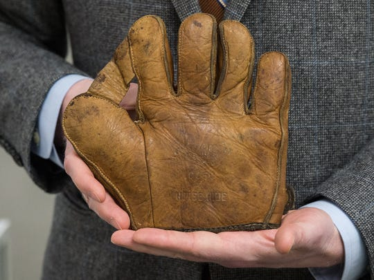 Christopher Harrington, Interim Dean, School of Education, Social Science and The Arts at UMES, holds an antique baseball glove at Salisbury Art Space on Friday, Feb. 23, 2018.