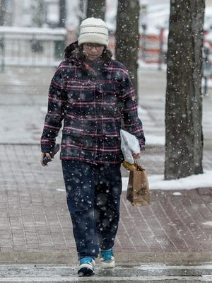 Katherine Odanaka from East Lansing shops the downtown in Lansing as the first snowfall of the season blankets the area Saturday, November 21, 2015.
