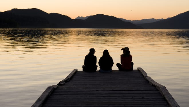 A trio of girls watch the sun set on Whitefish Lake.