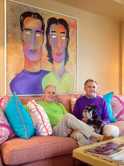 Jim Harness and Rick Kennedy with miniature schnauzer Bella in front of an artist rendering from a photo of them. In the art, the order is switched, and they are wearing opposite colors