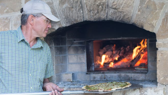 Geyer's Oven owner Dave Geyer working the Brick wood fire oven. He and his wife Anna built this oven 10 years ago.