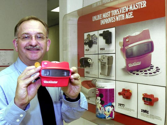 Mattel General Manager Dan Nottage holds a ViewMaster in front of a display showing the 3D viewing machines' evolution at the ViewMaster factory in Beaverton, Ore., Wednesday, Aug. 23, 2000.  Later this year, Mattel Inc. will close the Beaverton plant where the 60-year-old  toy has been manufactured for more than three decades,  lay off the last 60 workers and move production to Tijuana, Mexico.(AP Photo/Don Ryan)