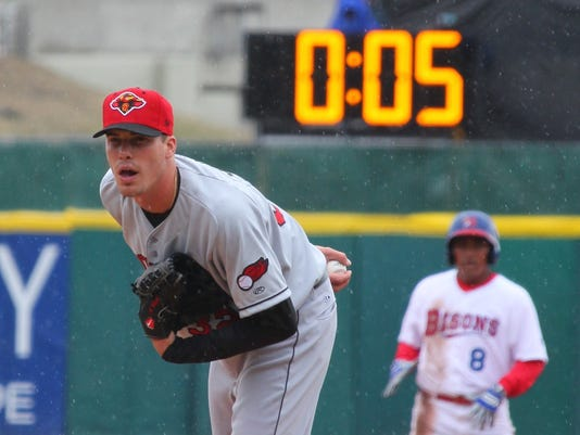 FILE - In this April 9, 2015, file photo, Rochester Red Wings pitcher Alex Meyer (32) looks in for a signal as a 20-second pitch clock is used for the Triple-A baseball opener between the Buffalo Bisons and Rochester Red Wings, in Buffalo, N.Y. This season, every minor league game that is tied after nine innings will begin each extra inning with a runner on second base. In baseball, runners are not awarded bases for no reason. They earn their way there. Not this season. Not in the minor leagues. Forget hits, runs and errors. Welcome to the baseball's brave new world where we are in a hurry to get done with the game.  (AP Photo/Bill Wippert, File)