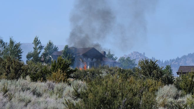 The James Loop Fire, started by construction equipment, burns near a home close to the town of Genoa on Monday, July 9.