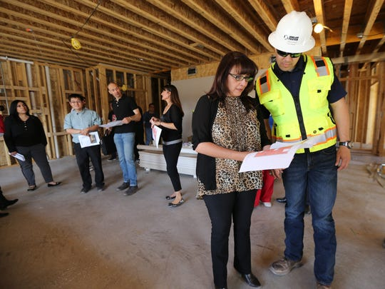 Project manager Roman Marquez and Jackie Leyva go over plans for the Artspace El Paso Lofts on Thursday during a tour.
