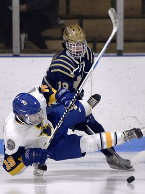 Irondequoit's Trevor Byrnes is checked by Notre Dame of Batavia's Ryan Antinore at Lakeshore Hockey Arena on Saturday, Dec. 3, 2016. Notre Dame of Batavia beat Irondequoit 3-2.