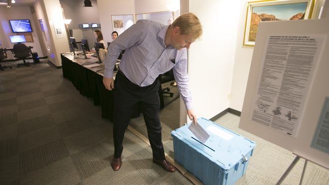 Lee Andelin of Gilbert places his ballot in the box for the Salt River Project elections Tuesday. Unofficial results show two solar-power advocates won election to the electric utility.
