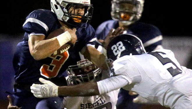 Blackman's Taeler Dowdy (3) runs the ball as he is tackled by Siegel's Gef Elder (12) and Kedron harper (5) during the palyoff game at Blackman, on Friday, Nov. 13, 2015.