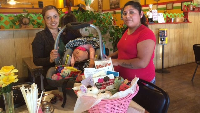 Lola Garcia, left, presented a Welcome Basket to Baby Valeria and her mother Mitzi Hernandez. The baskets are provided by the Arc of New Mexico which provides the baskets exclusively for families living with Down Syndrome.