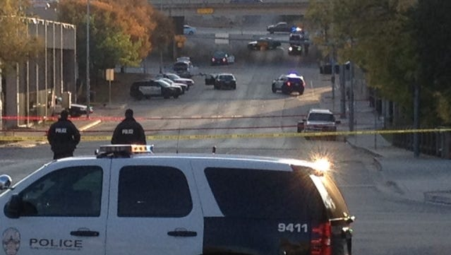 Police tape marks off the scene after authorities shot and killed a man who they say opened fire on the Mexican Consulate, police headquarters and other downtown buildings early Friday in Austin, Texas. In the distance, police cars surround the suspect's vehicle parked near the Interstate 35 overpass.