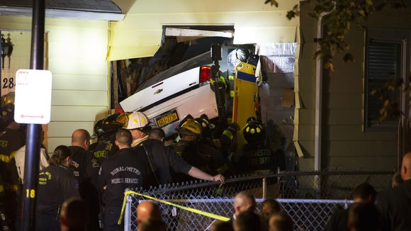 Rochester firefighters prepare to extricate a man after a car went into his home on Ferncliffe Drive on Oct. 8.