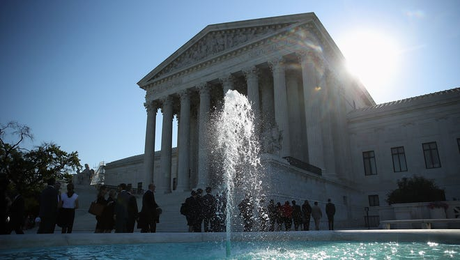 People wait in line to enter the Supreme Court building on June 20, 2016, in Washington.