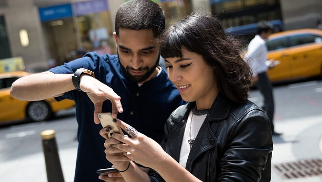 Sameer Uddin and Michelle Macias play Pokémon Go on their smartphones outside of Nintendo's flagship store, July 11, 2016 in New York City.