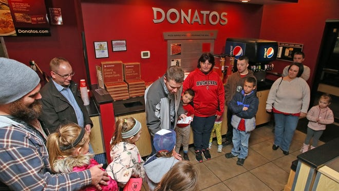 Brian Crumley, center, owner of Donatos on North 21st Street, hands Ohio State vs. Michigan football tickets to Lincoln White, 5, of Newark. Families of Lincoln White, Alison Armstrong, 6, of Newark, and William Lockhart, Jr., 15, of Utica, received tickets to the game donated by Donatos and the Christopher Carlson Foundation during a gathering Wednesday night.