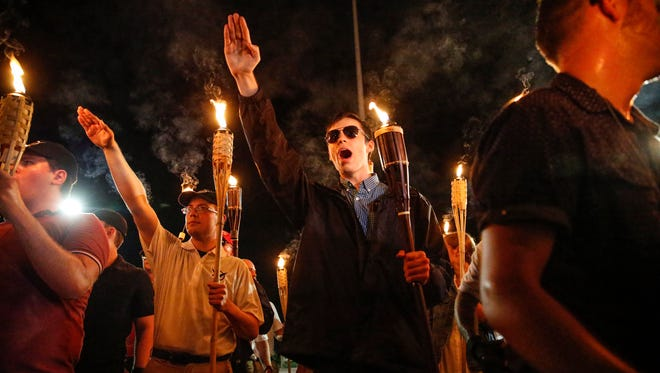 White-nationalist groups marched with torches through University of Virginia campus in Charlottesville on Aug. 11, 2017. When met by counter protesters, tempers turned into violence.