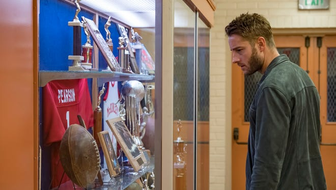 Kevin (Justin Hartley) looks at his high school football memorabilia in Tuesday's episode of NBC's 'This Is Us.'