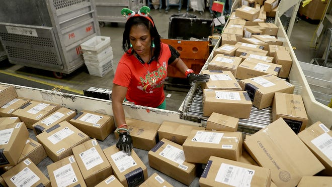 Mail handler Barbara Lynn sorts boxes at the Postal Service's Royal Palm Processing and Distribution Center on Dec. 4, 2017, in Opa Locka, Fla.