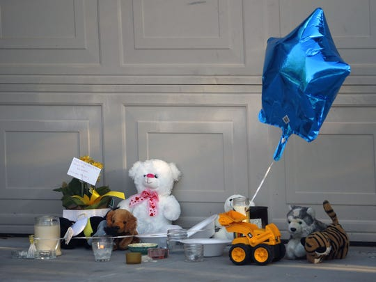 A memorial in front of a home Monday, Aug. 8, 2016, in Youngtown. A 16-year-old Youngtown boy is believed to have stabbed to death his 3-year-old brother and attacked his 9-year-old sister on Saturday night at the home.
