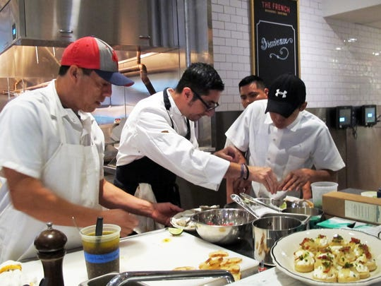 Chef-owner Vincenzo Betulia, center, prepares appetizers with his team in the open kitchen at a pre-opening event at The French, 365 Fifth Ave. S., Naples.