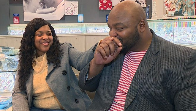 Derrick Markray kisses the hand of fiancee Amber Vinson after they selected a replacement engagement ring.
