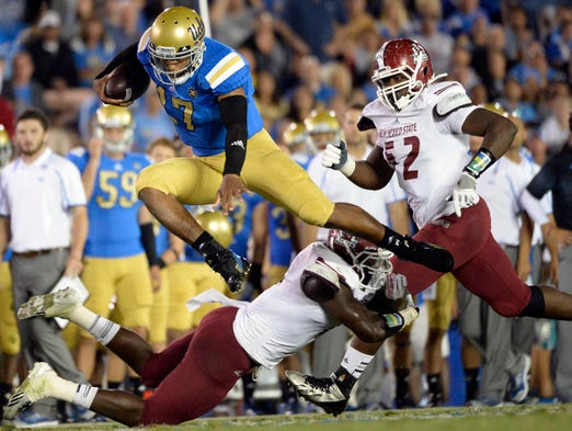 UCLA Bruins quarterback Brett Hundley leaps over a New Mexico State Aggies defender during the game at the Rose Bowl.