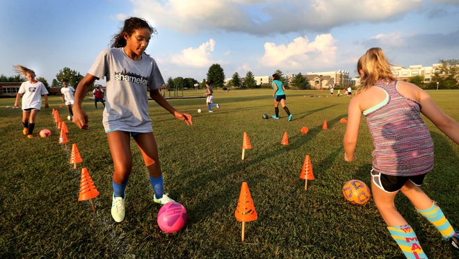 Jadyn McAboy, 10, left and Katie Hodge, 10, Thursday practice their dribbling with other members of their team at the soccer fields behind Erma Siegel Elementary, one of the proposed park sites.