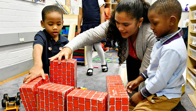 Pre-K co-teachers Rolanda SanMartin, center, works with students Josiah Angeles, left, and Christian Allen, right, as they build during afternoon work time at Hannah Penn K-8 School in York, Pa. on Tuesday, Dec. 8, 2015. (Dawn J. Sagert - The York Dispatch)