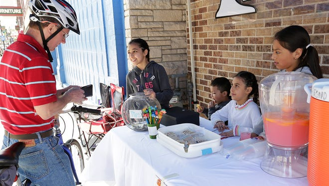 Charlie Schneider of Fond du Lac buys some refreshments from Saray Cortes, Dylan Santana, Najely Cortes and Carla Bivian at their lemonade stand in front of Mix It Up Bakery on Main Street Saturday. The city's  annual Lemonade Day gives kids the opportunity to learn the basics of running a business.