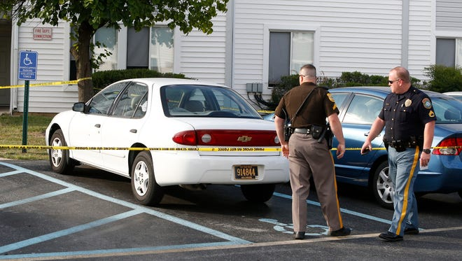 Police work at the Wilton Club Apartments after a shooting victim was found at the complex near New Castle late Saturday afternoon.