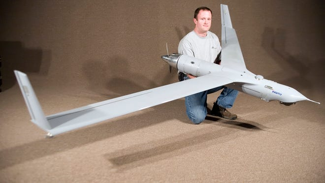 Insitu demo team specialist Brian Jones displays a drone aircraft in Bingen, Wash. Australian company Orbital, that makes engines for aerial drones, is planning to set up a facility in the Columbia Gorge.