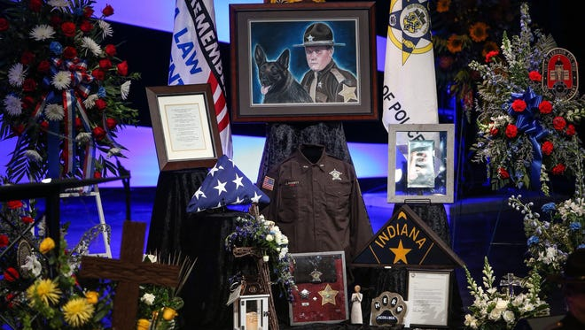 A memorial for Deputy Jacob Pickett sits along the stage during the funeral ceremony at Connection Pointe Christian Church in Brownsburg, Ind., on Friday, March 9, 2018.