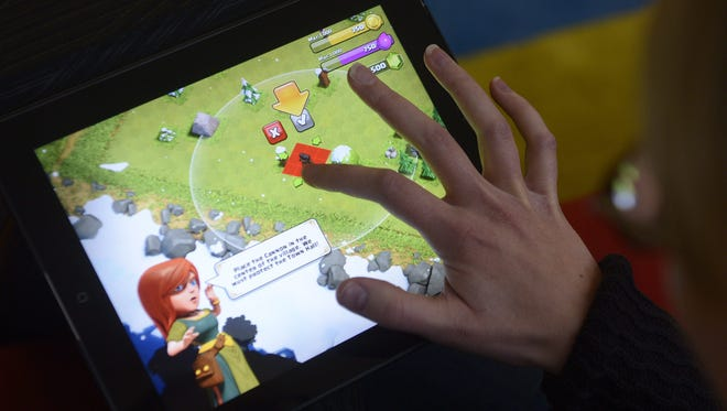 A woman plays the 'Clash of Clans' game of Finnish computer game maker Supercell on a tablet computer on December 14, 2012 in Helsinki.