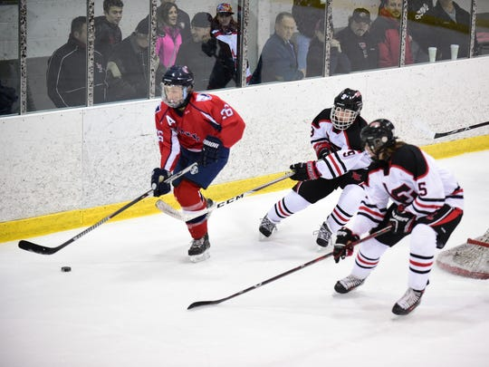 Livonia Franklin's Trevor Van Vliet (26) tries to control the puck, while Livonia Churchill players Matt Gibboney (5) and Donovan Young (9) give pursuit.