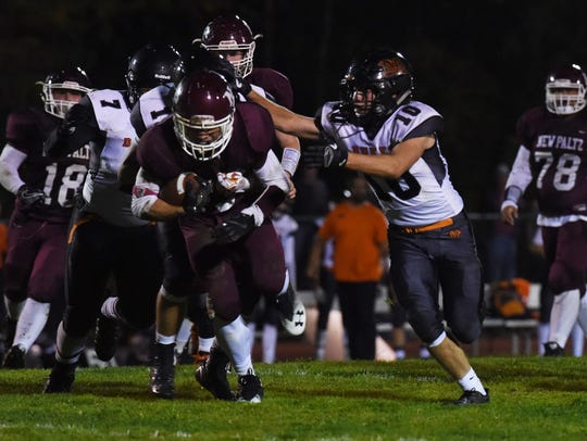 New Paltz's Axel Rodriguez, center, tries to get the