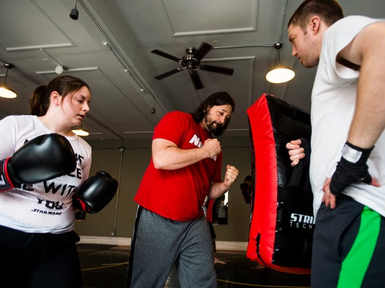 Joe Dressel teaches technique to students Olivia Sears, left, and William Sweeney, right, on April 12, 2016 at Hanover Boxing Club on Carlisle Street in downtown Hanover.