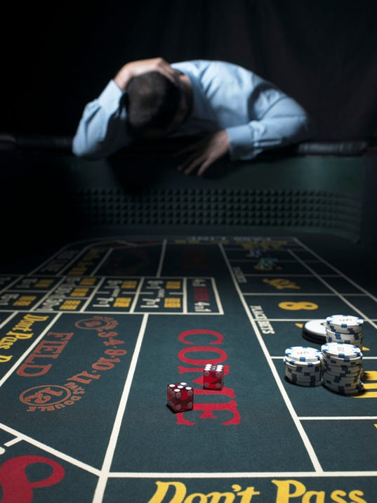 Man slumped at craps table, holding head (focus on table)