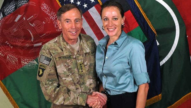 """This July 13, 2011 file photo, made available on the International Security Assistance Force's Flickr website, shows the former Commander of International Security Assistance Force and U.S. Forces-Afghanistan Gen. Davis Petraeus, left, shaking hands with Paula Broadwell, co-author of  """"All In: The Education of General David Petraeus."""" Petraeus resigned as CIA director over his extramarital affair with his biographer, Broadwell."""