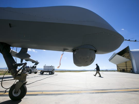 "Mechanics with General Atomics Aviation Systems walks by the Predator B"" unmanned aircraft at the Fort Huachuca U.S. Army installation in Sierra Vista."