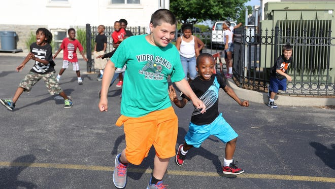 Andrian Forment , 12, a seventh-grader, and King Goodwin, 7, a second-grader, play a game of Sharks and Minnows at the start of the Yellow Bus Summer Camp Monday morning at St. Francis DeSales grade school in East Walnut Hills.