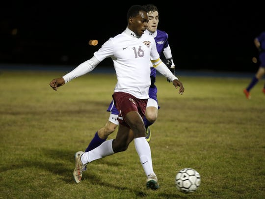 Florida High'€™s Michael Williams Jr dribbles past a Marianna defender during their District Semifinal game at Rickards High School on Wednesday.