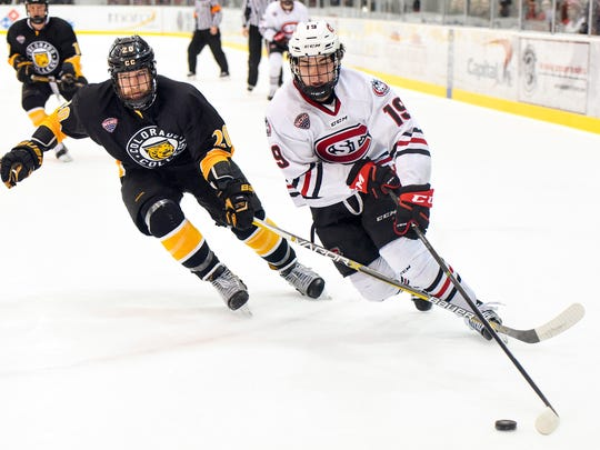 St. Cloud State's Mikey Eyssimont, 19, take the puck past Colorado College's Alex Pernitsky around the back of the goal during the first half Friday, March 3, at the Herb Books National Hockey Center.