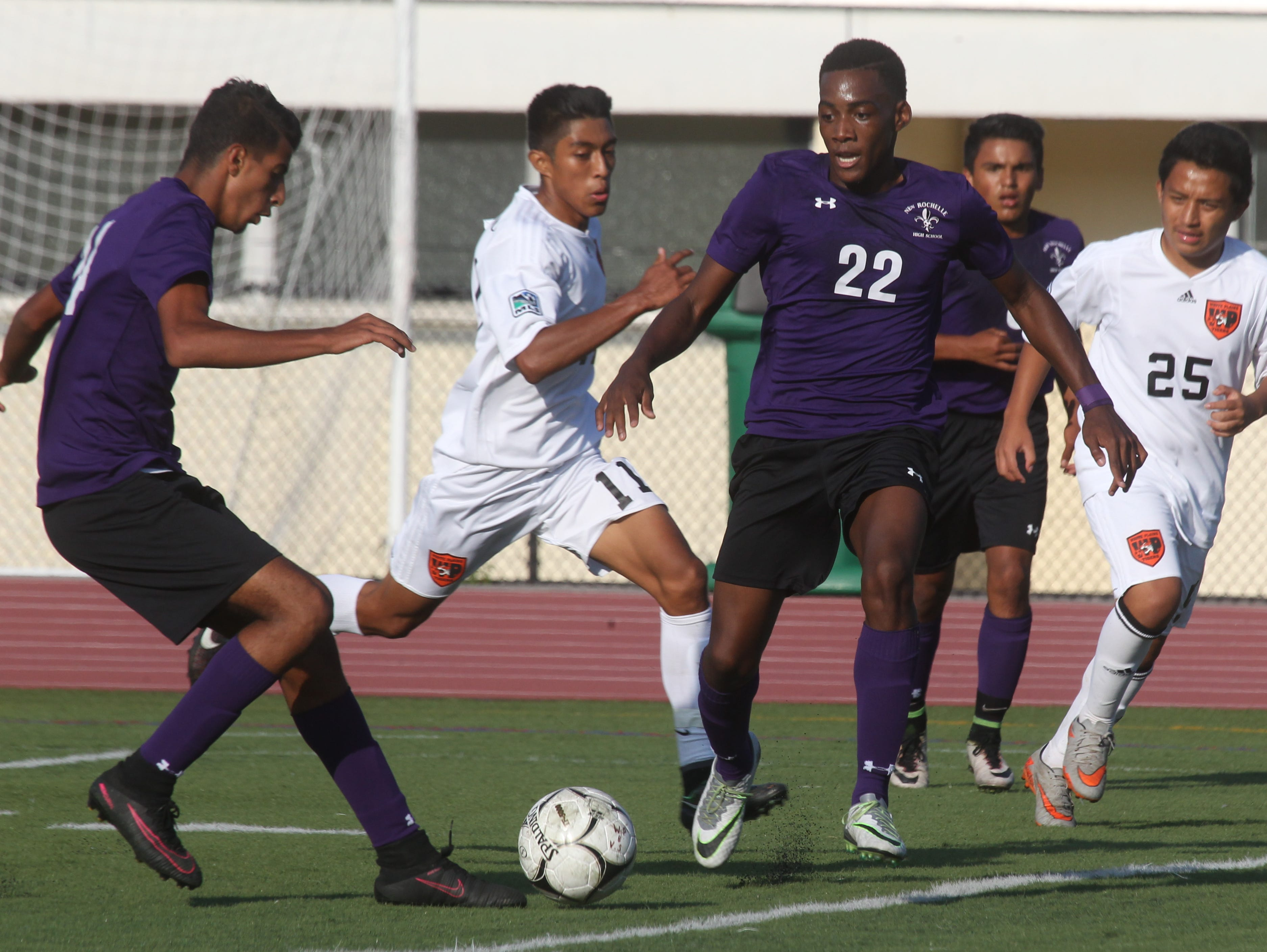 New Rochelle's Harwan Alzuabidi, left, and Tremaine Bryant (22) are pressured by White Plains' Levin Gramajio (11) during their game at White Plains Sept. 26, 2016. New Rochelle won 2-0.
