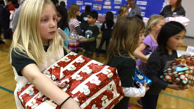 """Heather Thompson gathers presents that she and other Deerfield Elementary School students raised money to buy for needy local families for the holiday season. The money was raised through a school-wide """"penny war"""" run by Deerfield's first-graders, who were learning about empathy."""