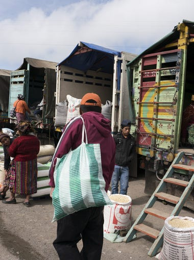 Native Guatemalans sell different kinds of grain and corn in the market. An average Guatemalan laborer makes $8 a day.