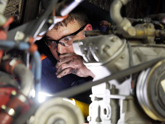Technician Nick Larry makes repairs on a bus that sits