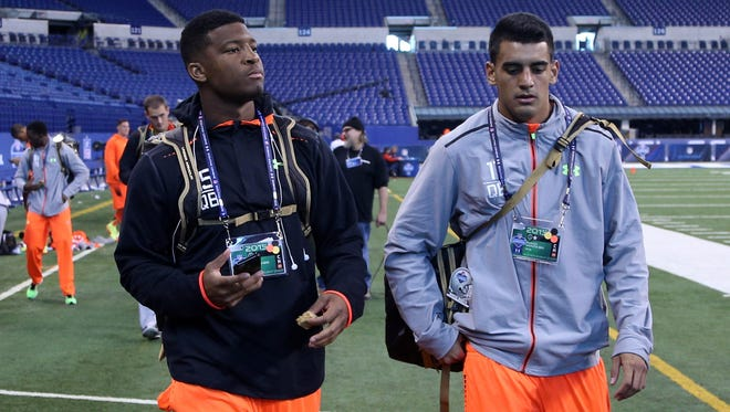Florida State quarterback Jameis Winston (left) and Oregon Ducks quarterback Marcus Mariota walk out together after finishing their workout during the 2015 NFL Combine at Lucas Oil Stadium.