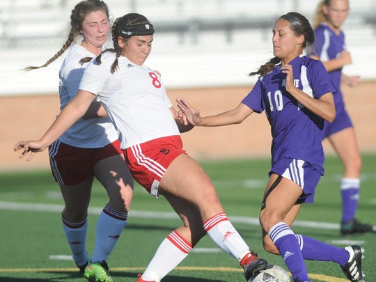 Wylie's Randie Dennison (10) battles Mineral Wells' Rachel Carter (8) for the ball. Mineral Wells won the Region I-4A quarterfinal playoff game 1-0 Monday, April 3, 2017 at Ram Stadium in Mineral Wells.