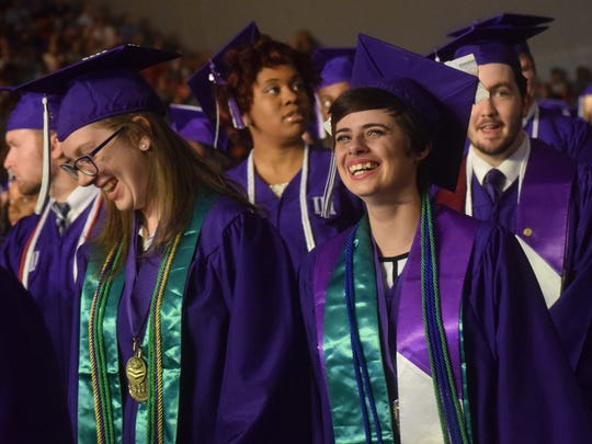 Zoe Barnett (left) and Paige Anderson, graduating seniors in the Louisiana Scholars' College of Northwestern State University in Natchitoches, smile at their commencement ceremony Friday.