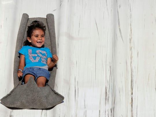 Dulce Torres, 5, of Sheboygan enjoys sliding down a